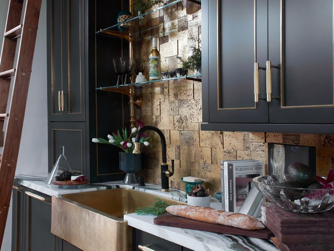 black kitchen with brass sink and rolling library ladder