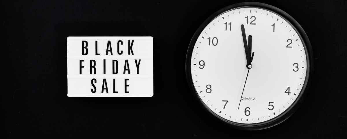 a black friday sale signage beside a black and white round analog wall clock