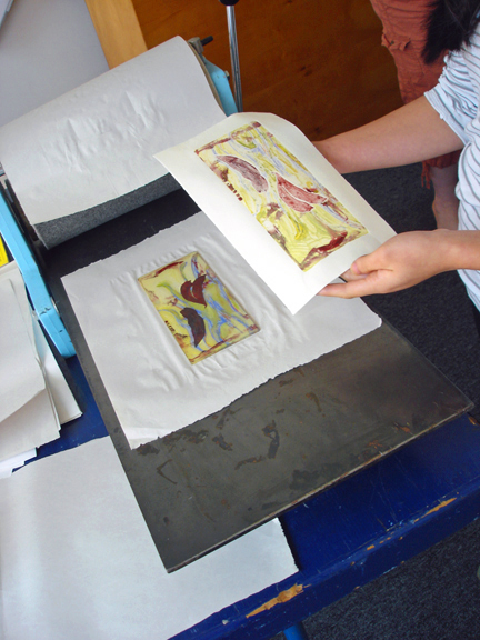 Artist pulling her print from the plate.