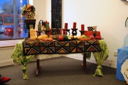 The Kwanzaa table is set at the Craft in America Center. On both ends of the table sit traditional hats created by LA's Hatzy Lady, Yvonne Lewis.
