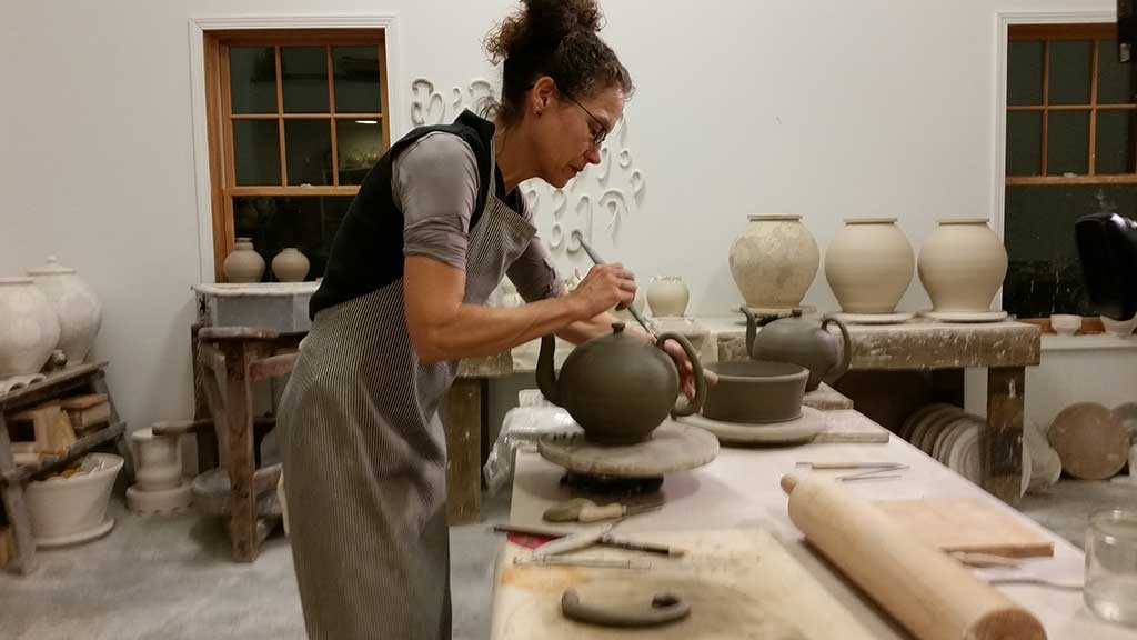 Linda Sikora works on a teapot in her studio
