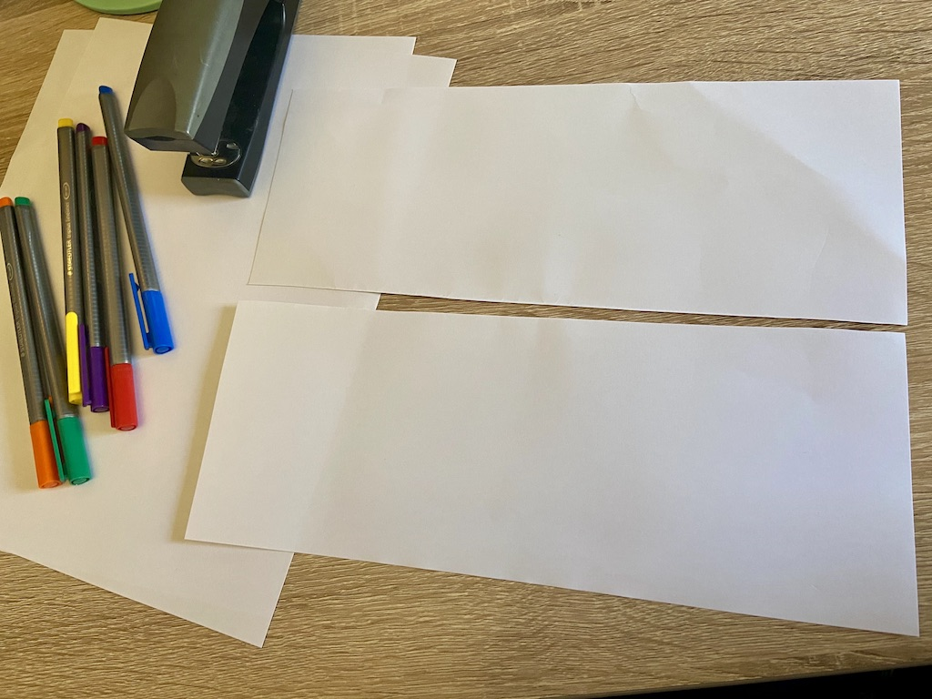 Cut (or fold and tear) a piece of paper in half lengthwise to make two long, skinny rectangles.