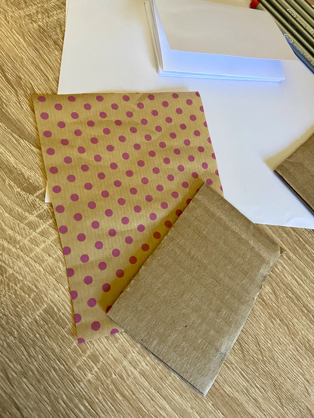 Take your decorative or scrap wrapping paper and cut two pieces a little larger than the cardboard, about an inch or two bigger on each side.