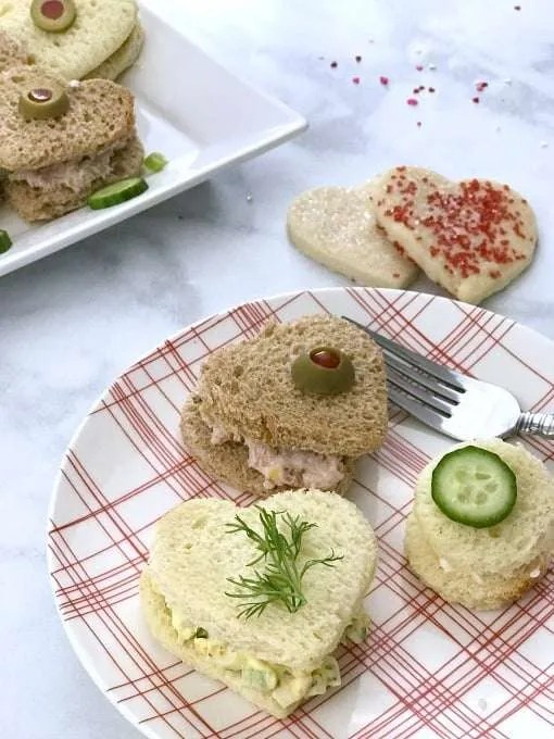 Valentines Party Tea Sandwiches heart shaped bread with olive, dill and cucumbers on top on a white and red plate on a white counter
