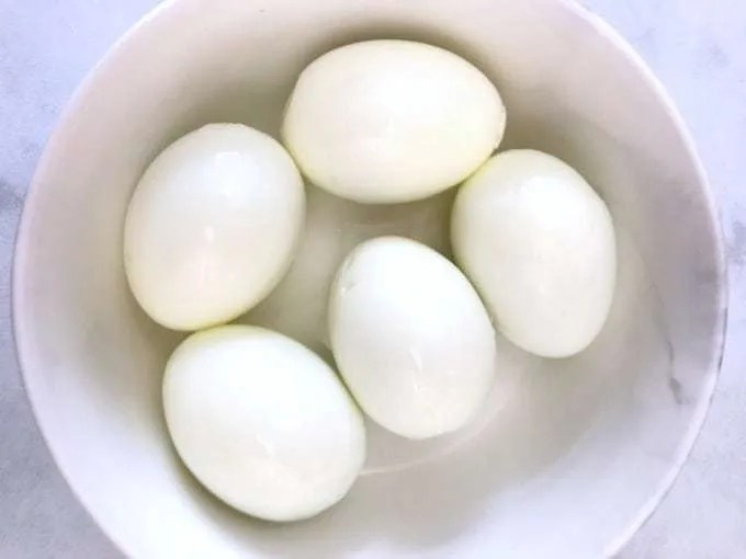 5 hard boiled eggs in white bowl on white counter