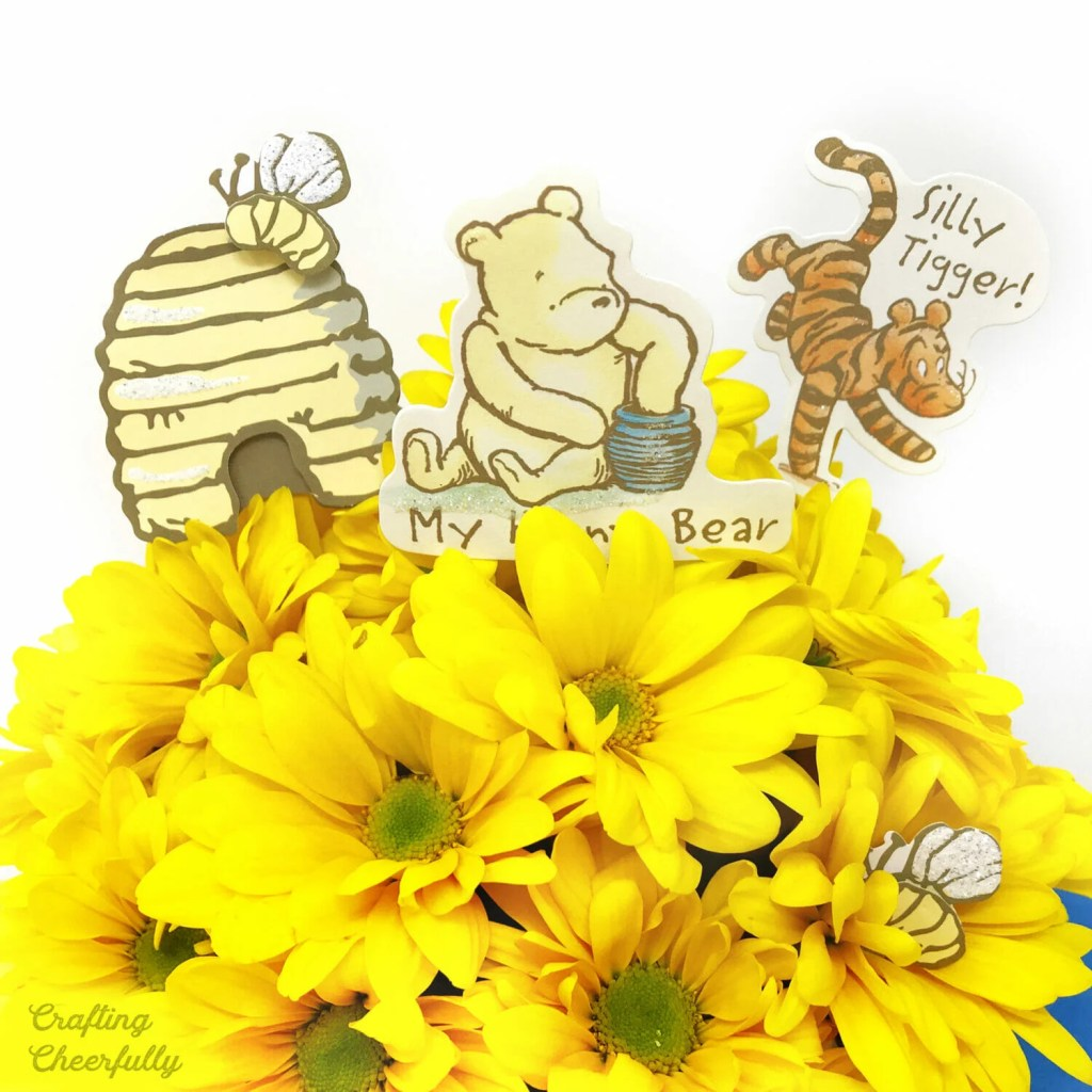 Terra cotta honey pot with yellow flowers and classic Winnie the Pooh characters.