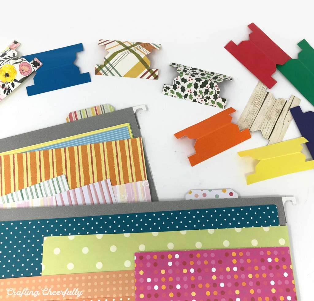 File tabs being inserted into file folders to organize scrapbook paper.