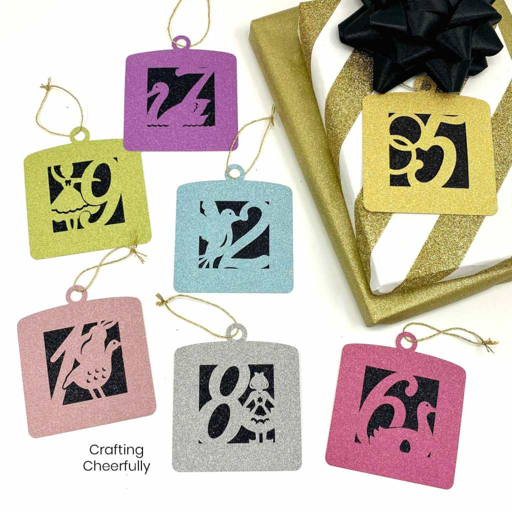 Square paper ornaments that are are also gift tags lay on a table next to gifts wrapped in gold. The ornament gift tags have numbers and a picture to match from the song 12 Days of Christmas.