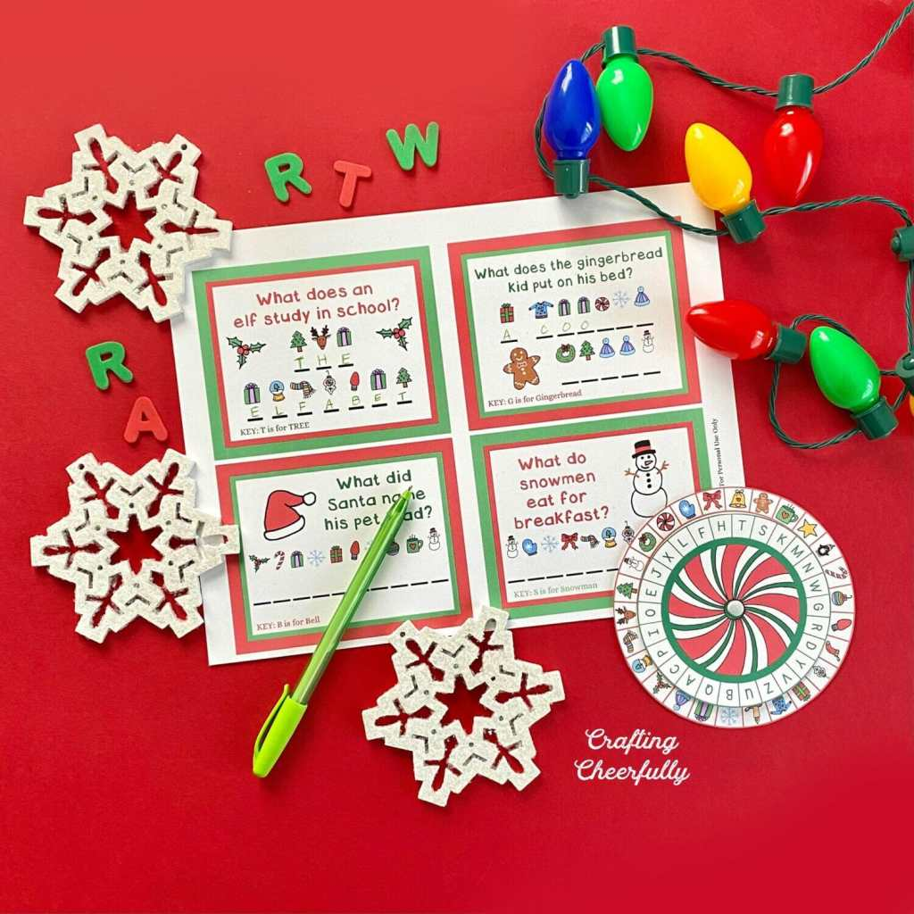 Secret decoder printables laying on a red table. Wooden snowflakes and a strand of holiday lights lay near it along with a green pen.