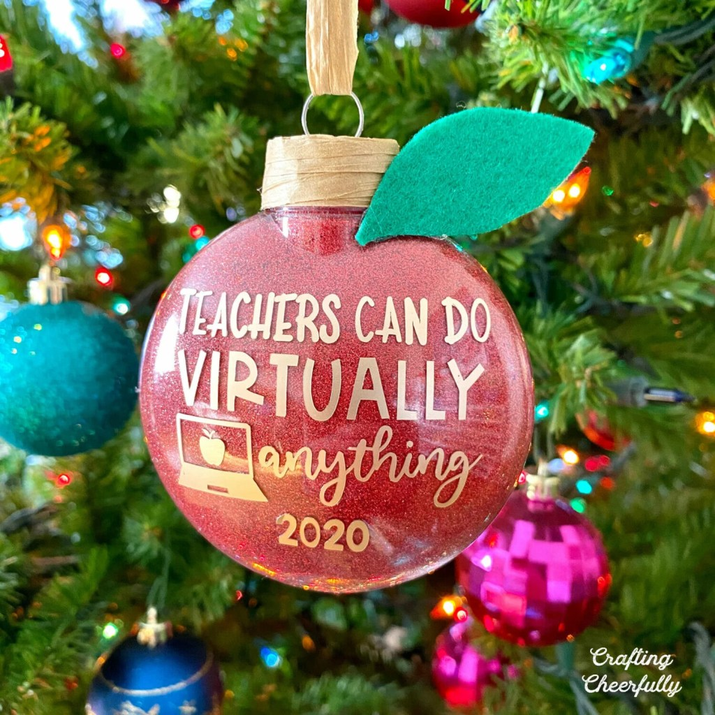"""A red glitter ornament hangs in a tree with a brown stem and felt leaf. Wording cut from gold vinyl on the front of the ornament reads """"Teachers can do virtually anything 2020"""" with a picture of a laptop."""
