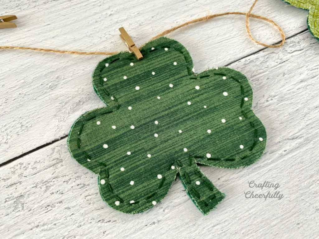 Shamrock made from green polka dot fabric lays on a white wooden table.