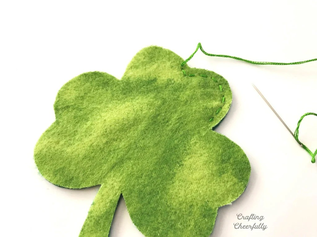 A fabric shamrock is being stitched around the edges with a needle and green embroidery floss.