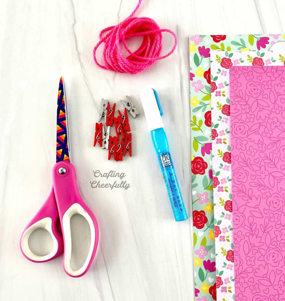 Supplies needed for Valentine's Day banner laid on a table. Scissors, clothespins, paper, yarn and glue pen.