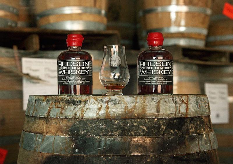 A bottle of hudson whiskey on a barrel