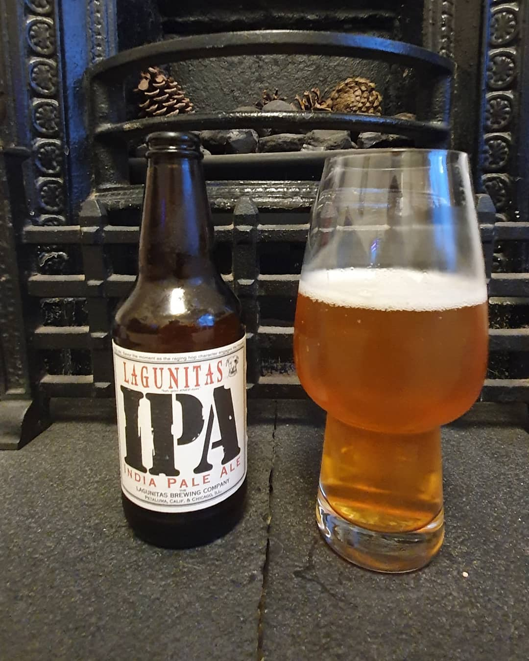 Lagunitas IPA poured into a beer glass sitting in front a fireplace