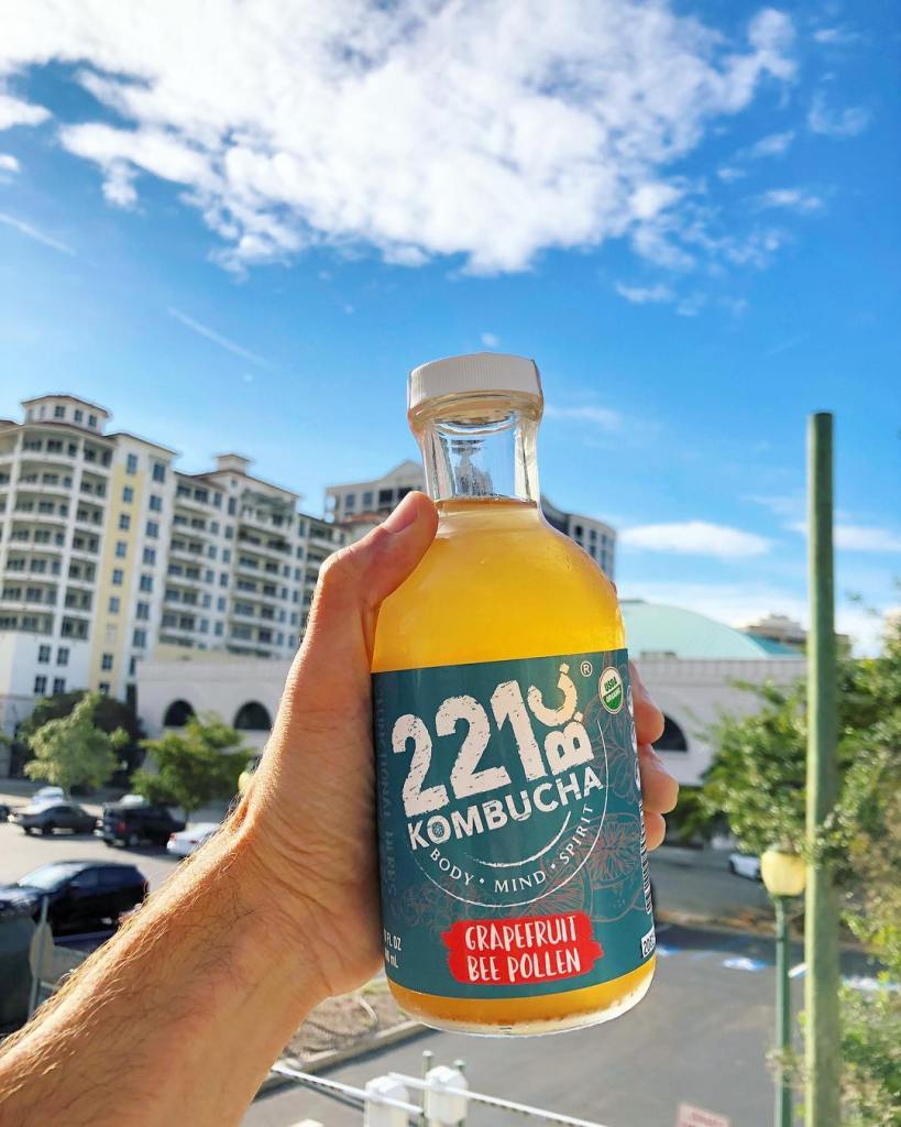 man holding a glass bottle of Kombucha221bc grapefruit bee pollen kombucha. A city background on a clear blue sky afternoon.