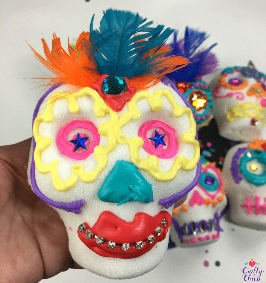 Sugar skull decorated with feathers, gems and rhinestones.