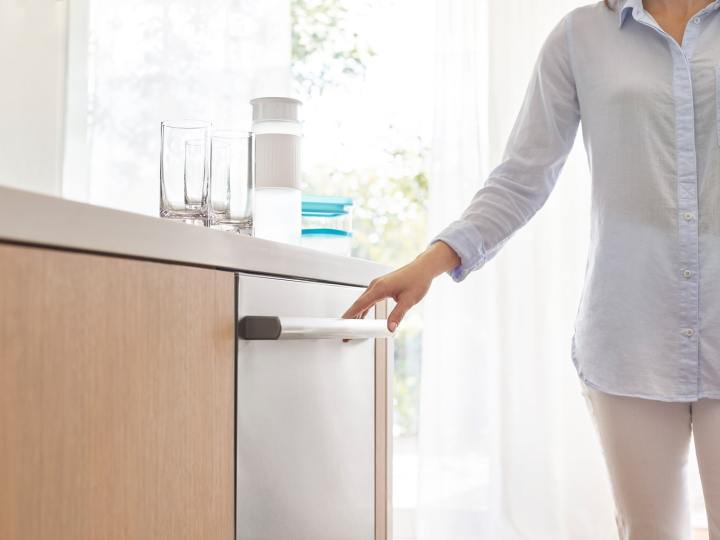 Woman standing next to a silver Bosch diswasher