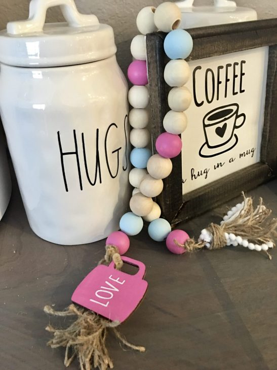Create this easy painted DIY Wood Bead Tassel Garland. You can make this using some items from the Dollar Tree, your local crafts and even with items from Amazon. Display the tassel bead strand with your home decor items, coffee mugs, and so much more. #diywoodbeadtassel #woodbeads #homedecordiy #woodbeadgarland #woodbeadgarlanddiy #woodbeadcrafts