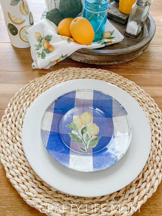 Create these stunning DIY Decoupage Plates using a few items from the dollar store. Learn how to decoupage and create beautiful looking plates for any season using this simple method. All you needs is a few items from the dollar store, and mod podge to get a store bought look! #modpodge, #decoupage #decoupageplates #modpodgeprojects #modpodgeplates #lemondecor #lemondiy #lemonplates #summerdecor #summerdiningroom #diningroom #diningroomdecor