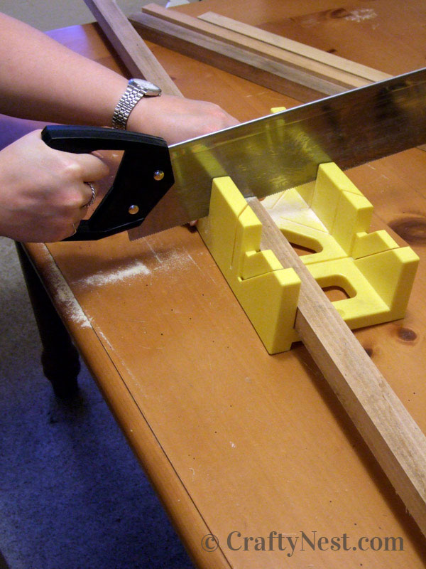 Cutting the bulletin board frame pieces with a miter box and pull saw, photo