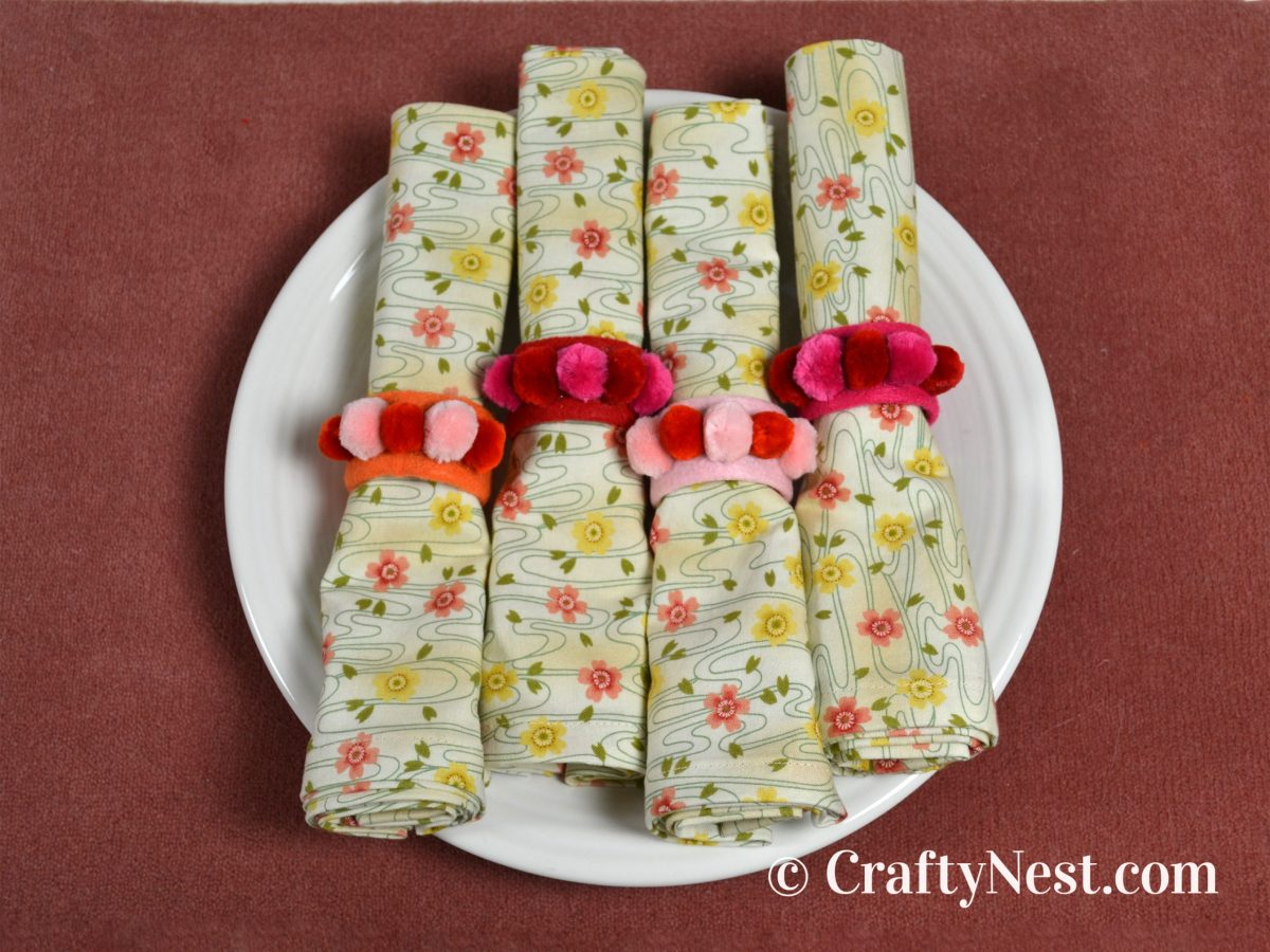 Four rolled cloth napkins with napkin rings, photo