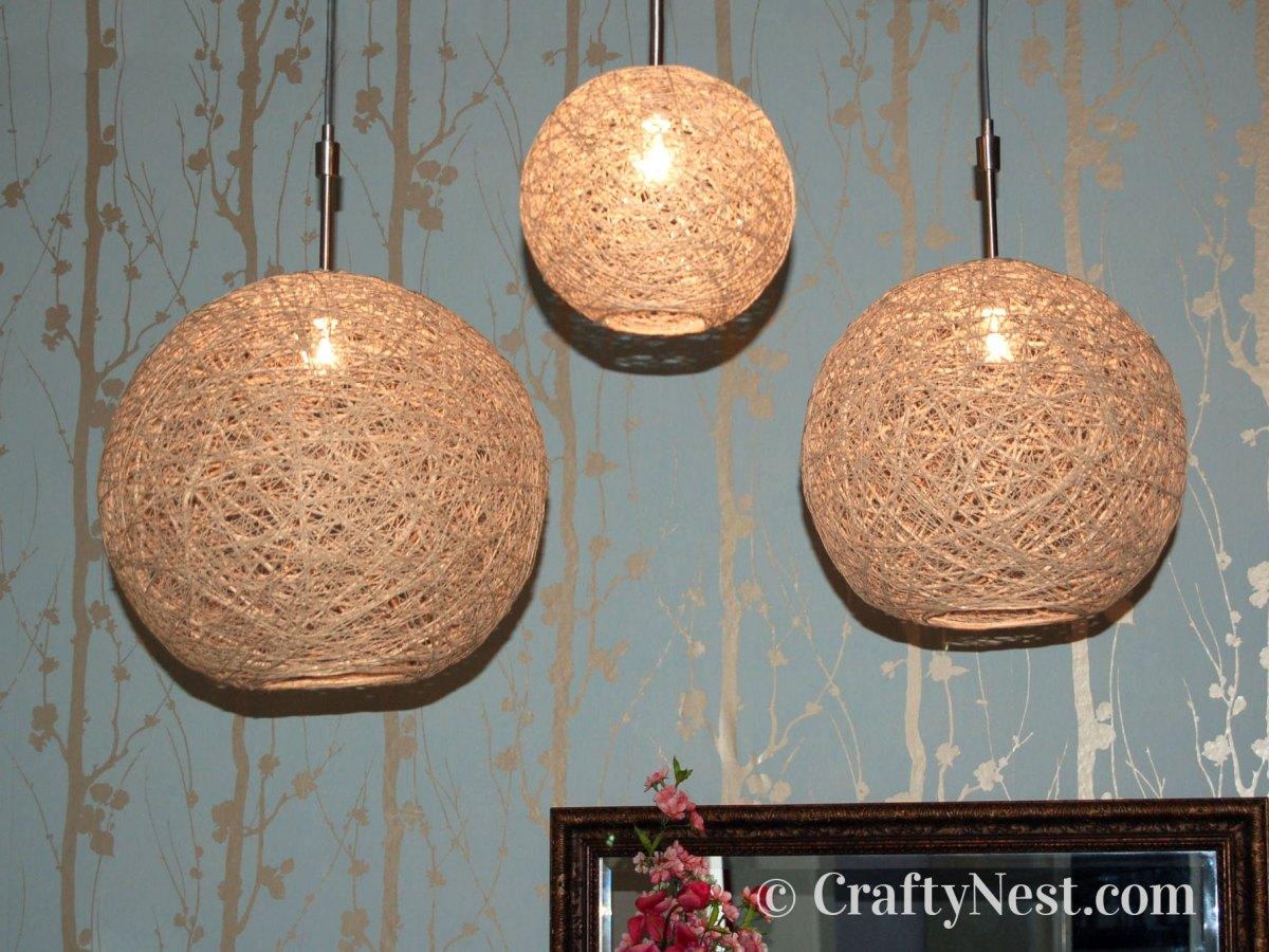 Three handmade hemp string pendant lamps with lights on, photo