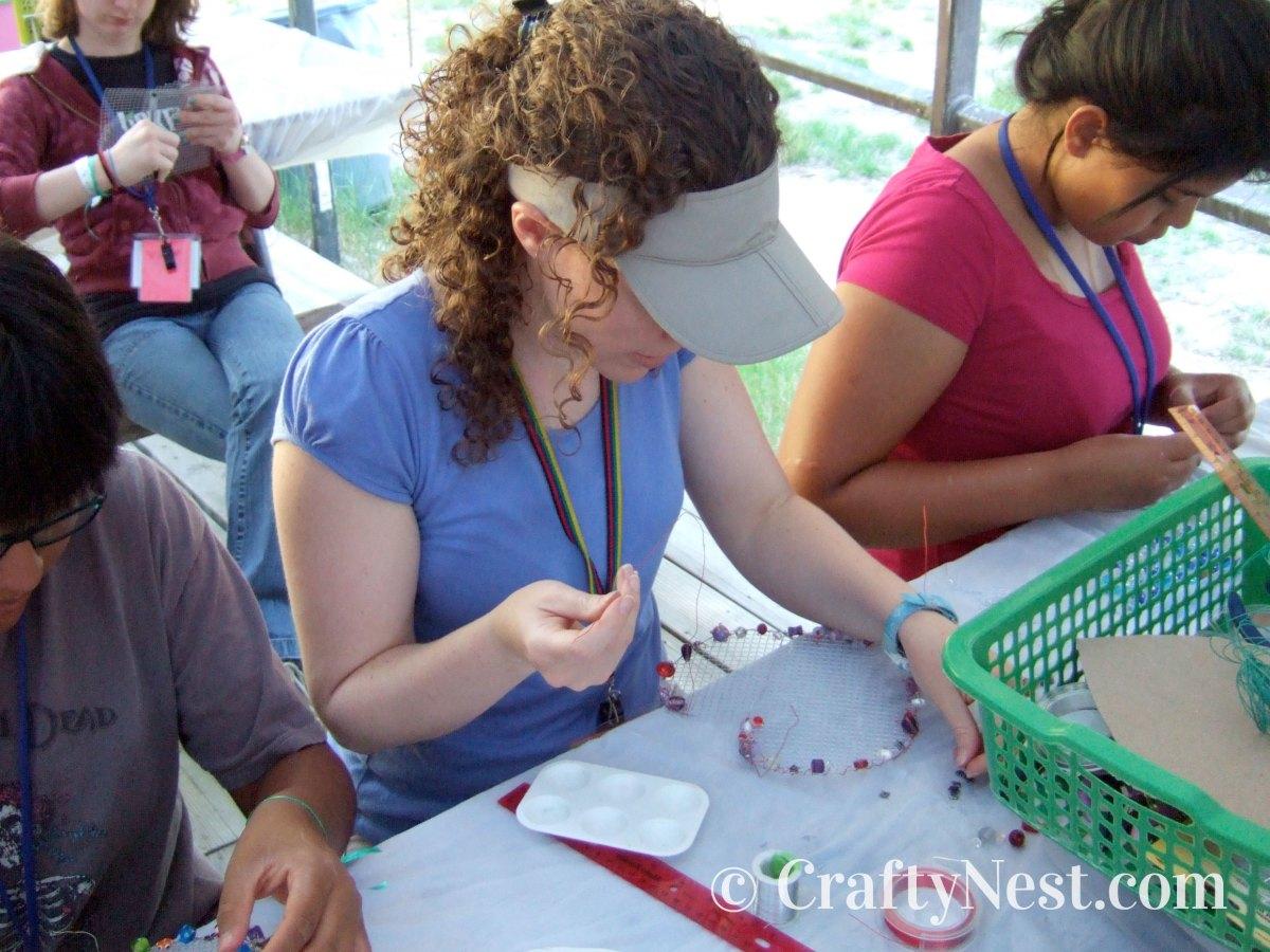 Girls making wire jewelry holders, photo
