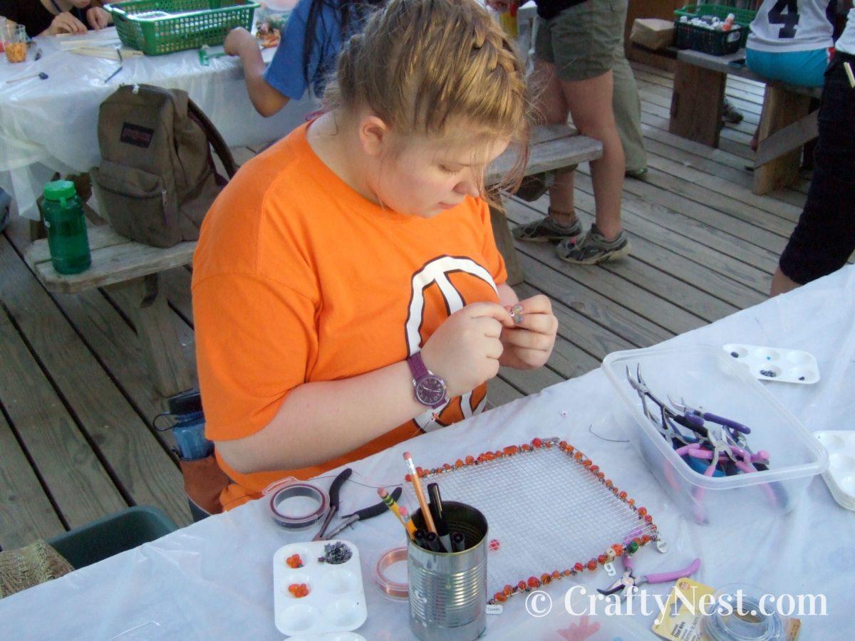 Girl making wire jewelry holders, photo