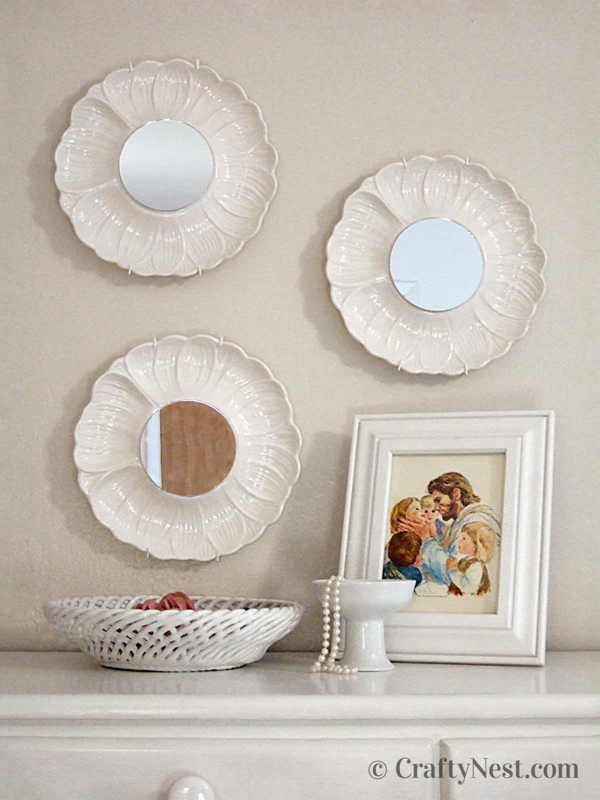 Three artichoke plates with mirrors hanging above a dresser, photo