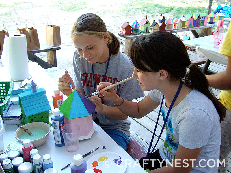 Two girls painting a birdhouse, photo