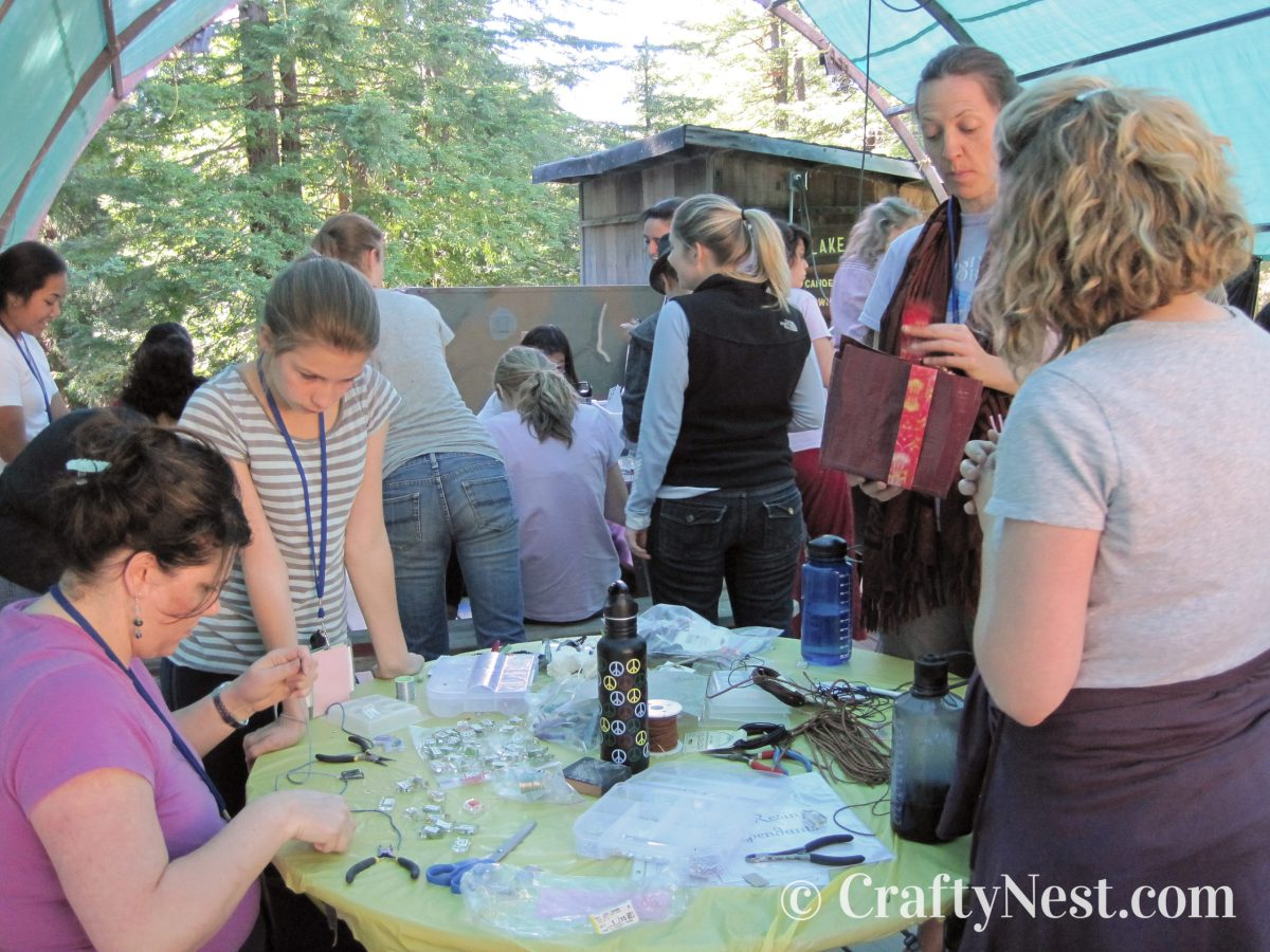 Girls and adults at camp making resin pendants, photo