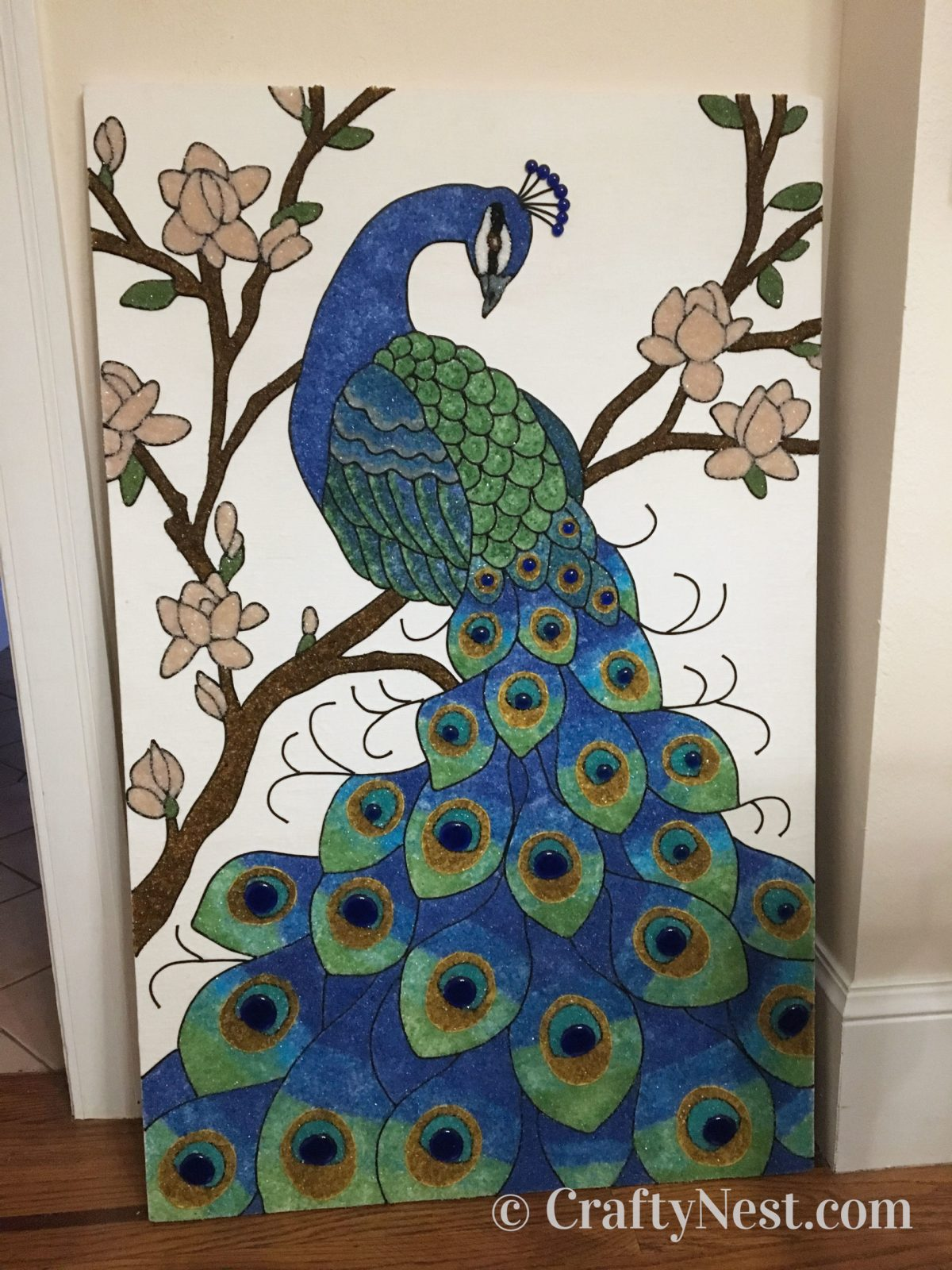 Peacock gravel art leaning against the wall, photo