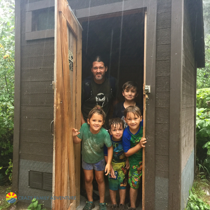 Taking cover from a down pour in an outhouse after hiking to Avalanche Lake