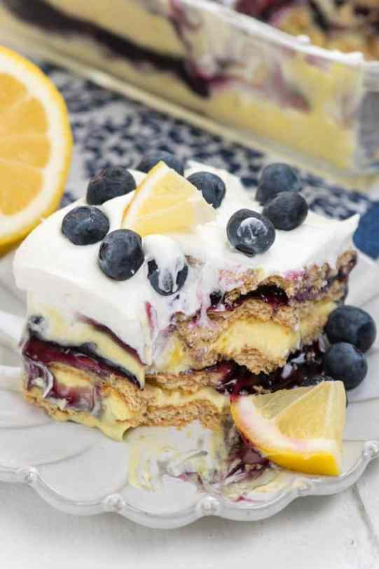 slice of lemon icebox cake on white plate with bite missing