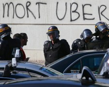 Police observe anti-Uber protests in Paris on 25 June 2015. Graffiti reads 'Death to Uber'. Photograph by Charles Platiau.