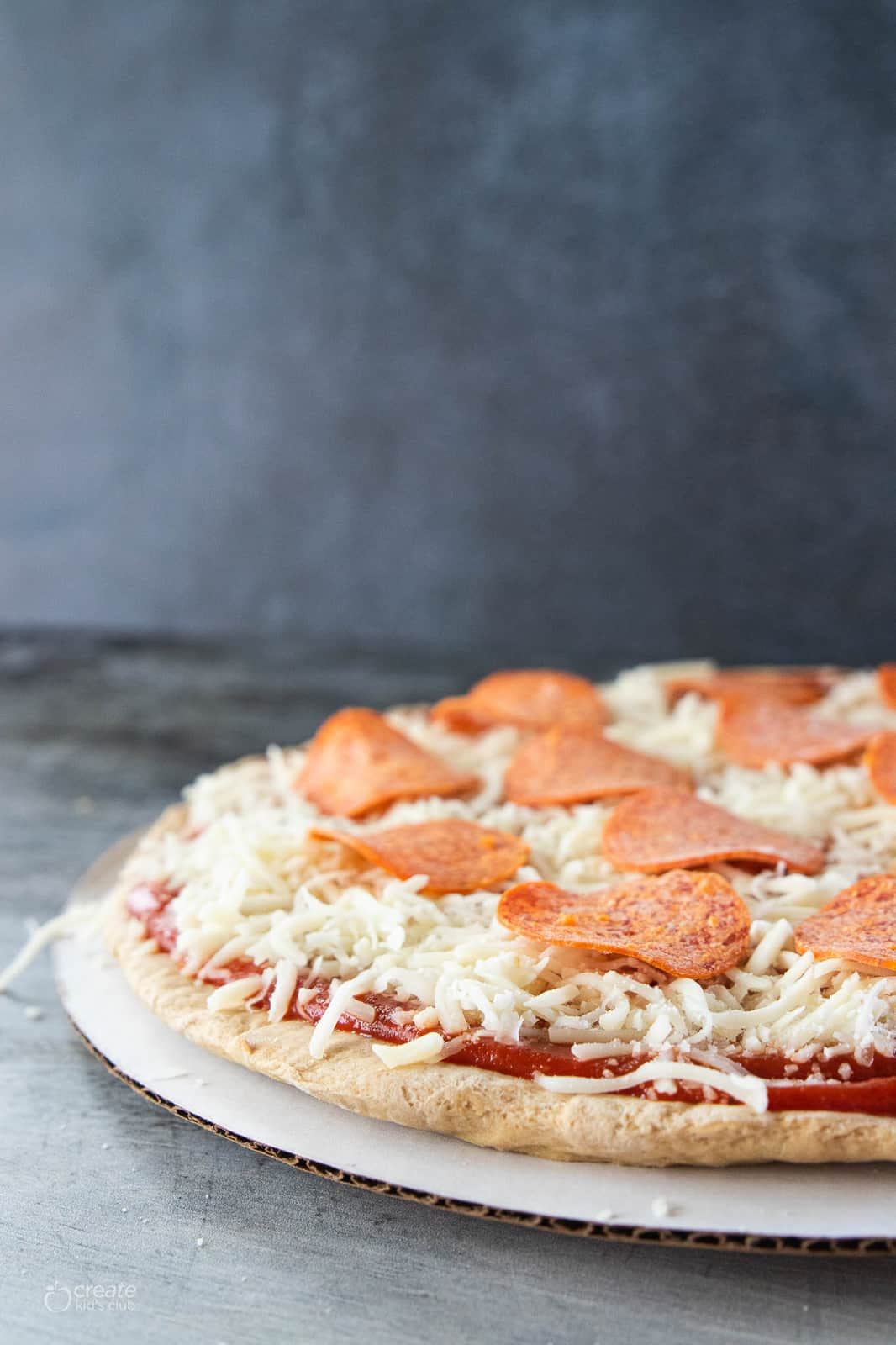 pizza crust dough topped with sauce, cheese and pepperoni