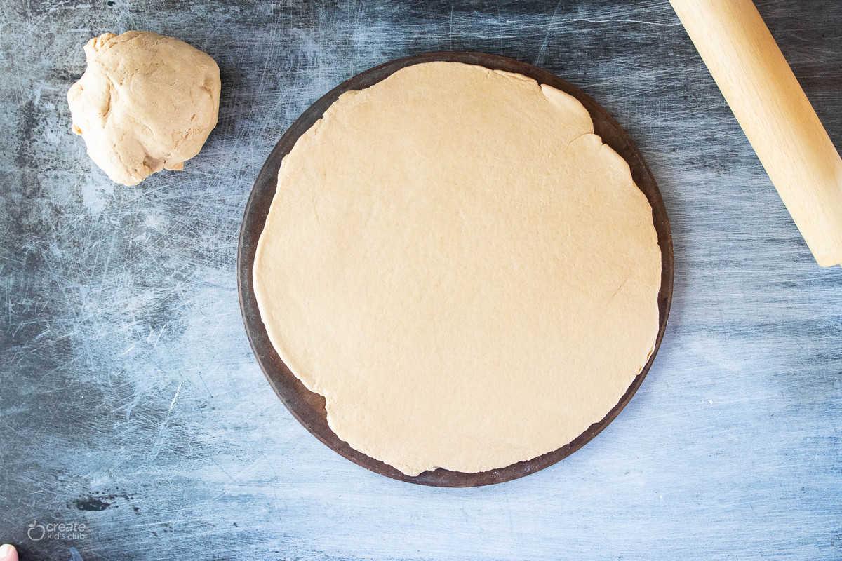 raw pizza crust on pizza round
