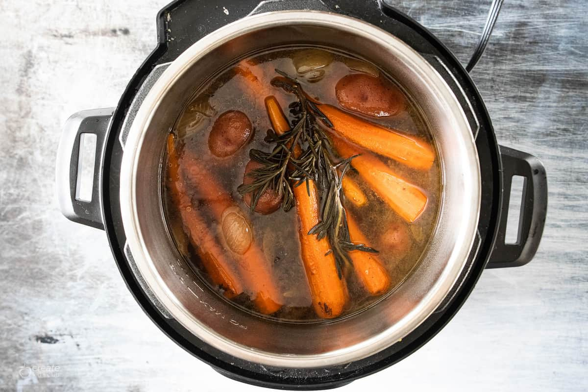 instant pot filled with herbs, vegetables and roast