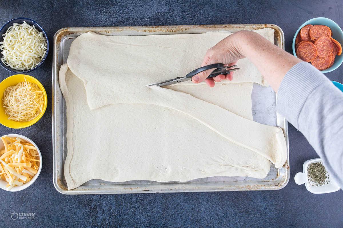 pizza dough on sheet pan being cut