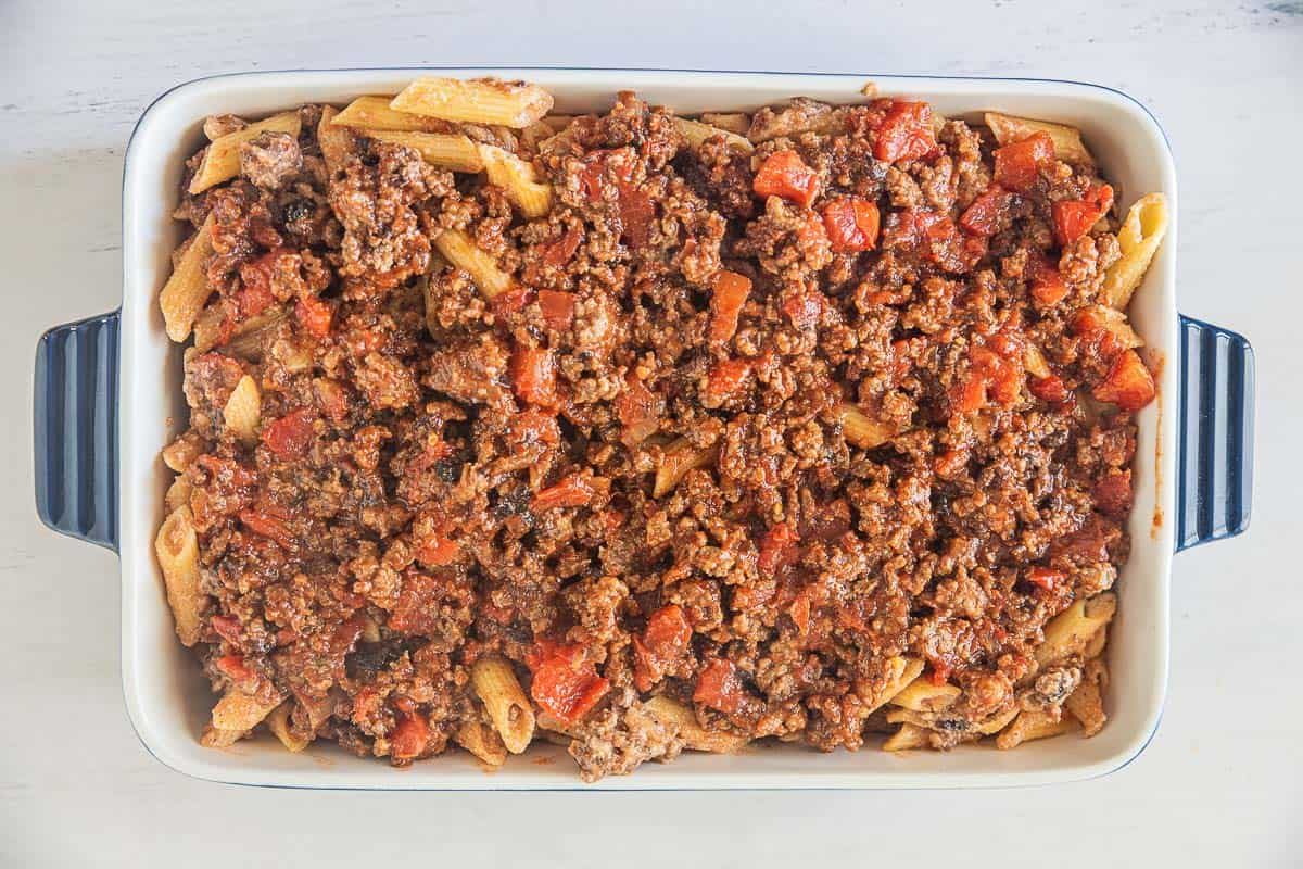 cheesy gluten free ziti in baking dish topped with sausage