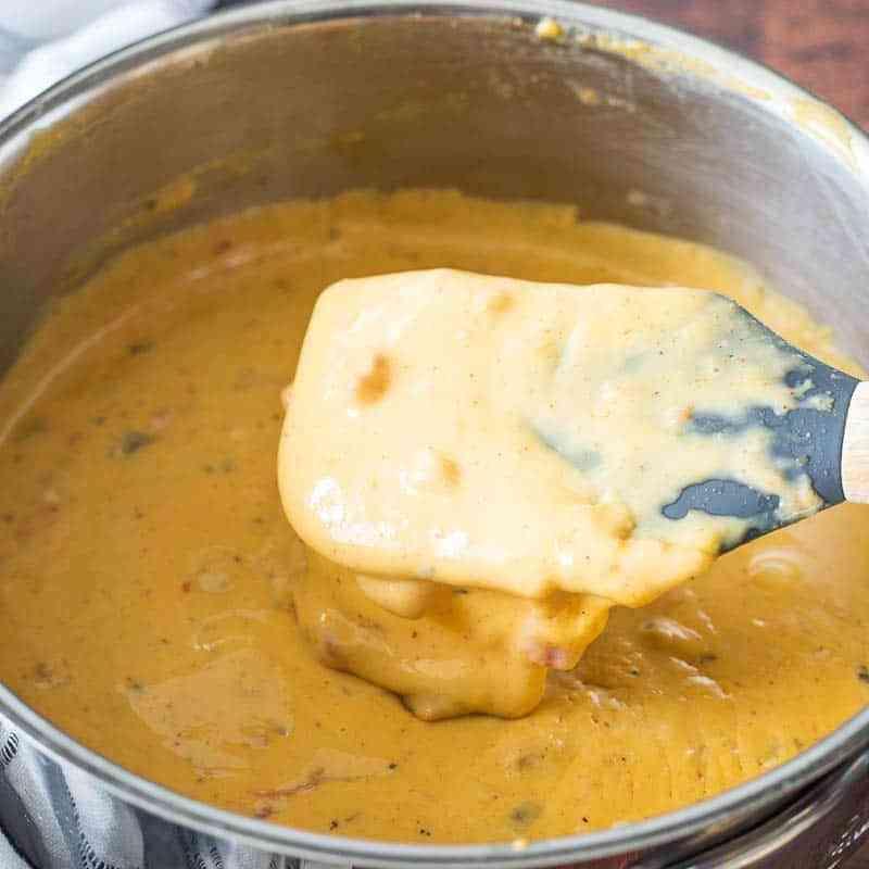 spatula stirring cheese sauce in sauce pan