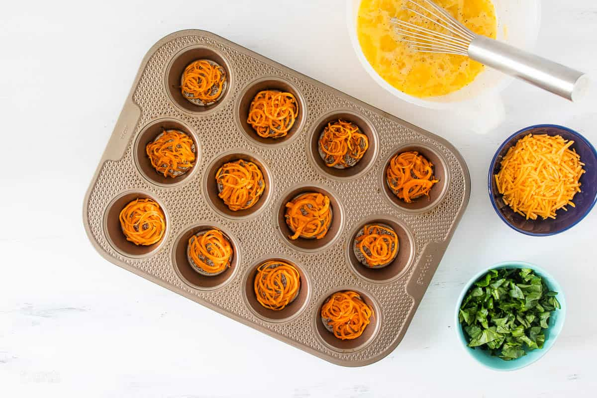 spiralized sweet potatoes at the bottom of a muffin tin