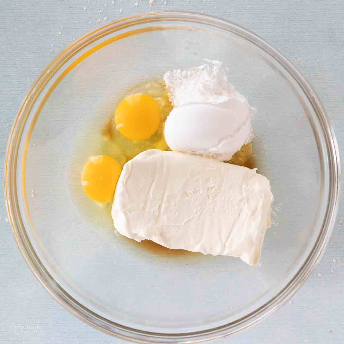 Cream cheese, eggs, and powdered sugar in a glass bowl.