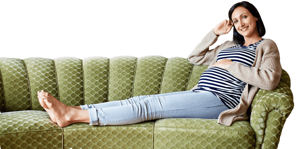 Portrait of a smiling pregnant woman sitting on her sofa