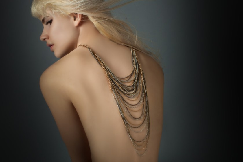 Blonde model wearing chain necklace down back.