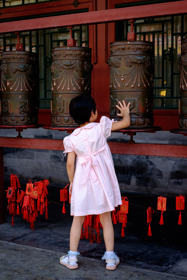 Chinese girl spinning prayer wheel in Prince Gong's mansion, Beijing, China