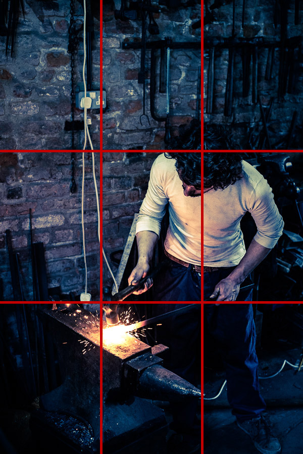 Portrait of blacksmith at work with anvil and hammer and rule of thirds grid