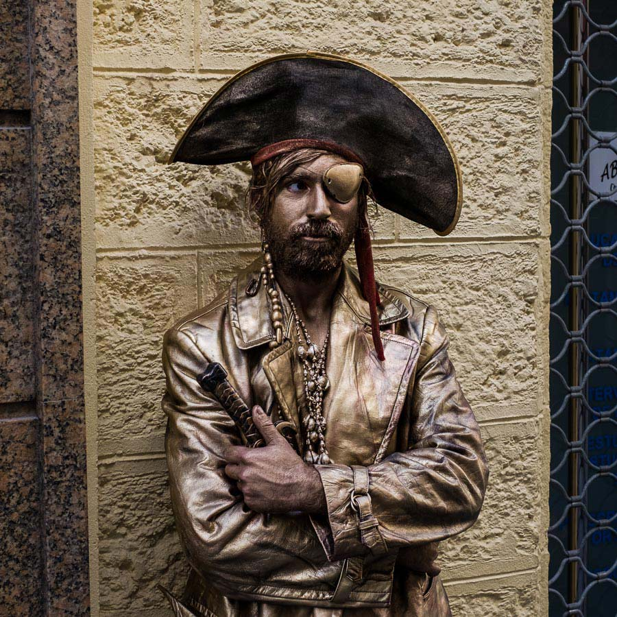 Street photo of man dressed as a pirate and painted in gold taken in Cadiz with a Fujifilm camera