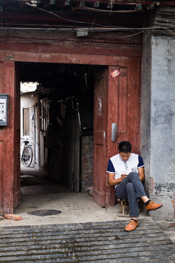 Street photo of a man sitting on a step in a hutong in Beijing, China